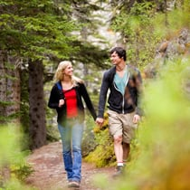 Male and female walking on wooded trail