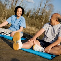 Asian couple sitting on yoga mats